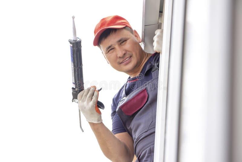 主要工作者在房屋建设亚洲人安装窗口基石修理胶合与硅树脂 库存图片