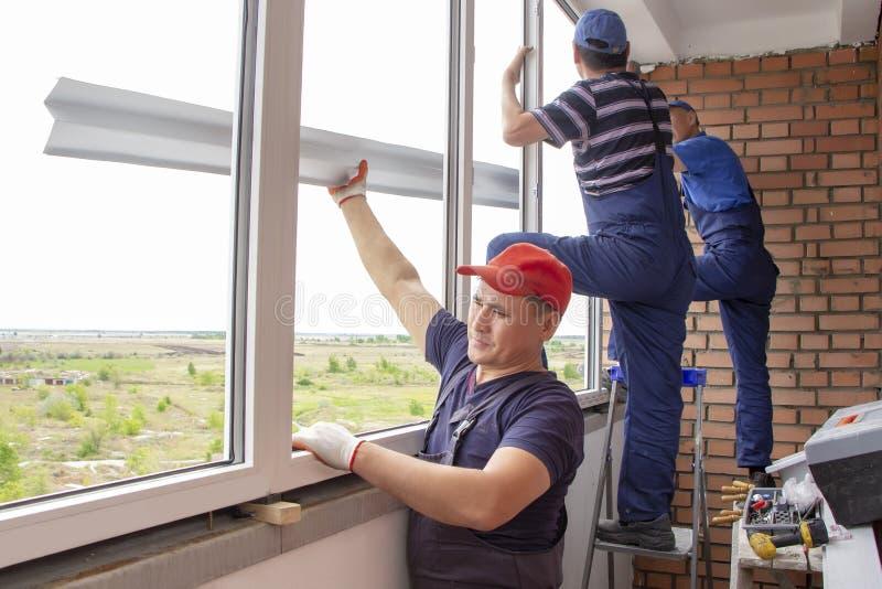 主要工作者在房屋建设亚洲人安装窗口基石修理 免版税库存照片