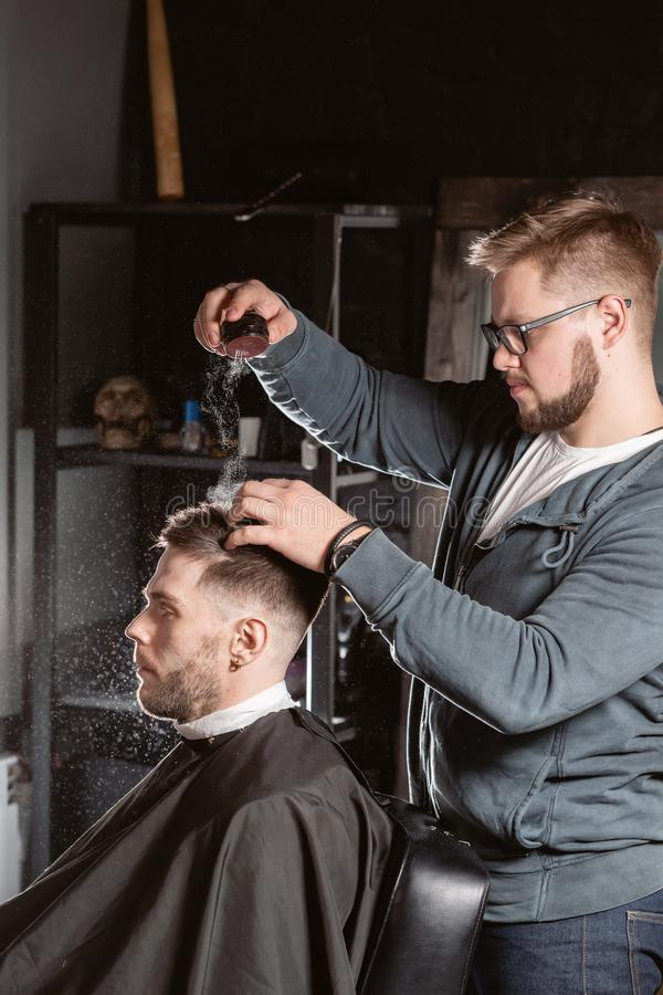 主要理发师倾吐称呼粉末修理头发 美发师做年轻人的发型 免版税库存照片