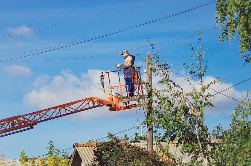 主要电工在街道上的工作在高度 免版税库存图片
