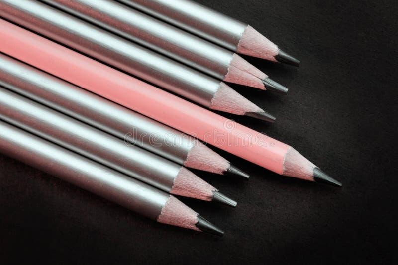 主角桃红色铅笔与其他不同在黑背景的银色铅笔 免版税库存图片