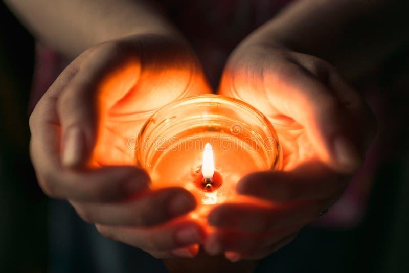 举一个升蜡烛的人杯在他们的手上 图库摄影
