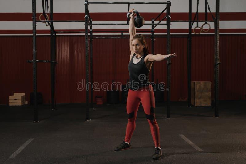 举一重量级的kettlebell的年轻crossfit妇女在健身房 图库摄影