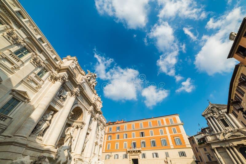 举世闻名的Trevi喷泉在与云彩的蓝天下 库存照片