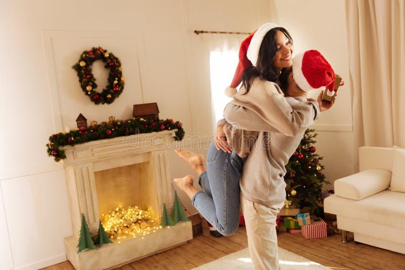 举他的妻子和拥抱她的爱恋的丈夫 图库摄影