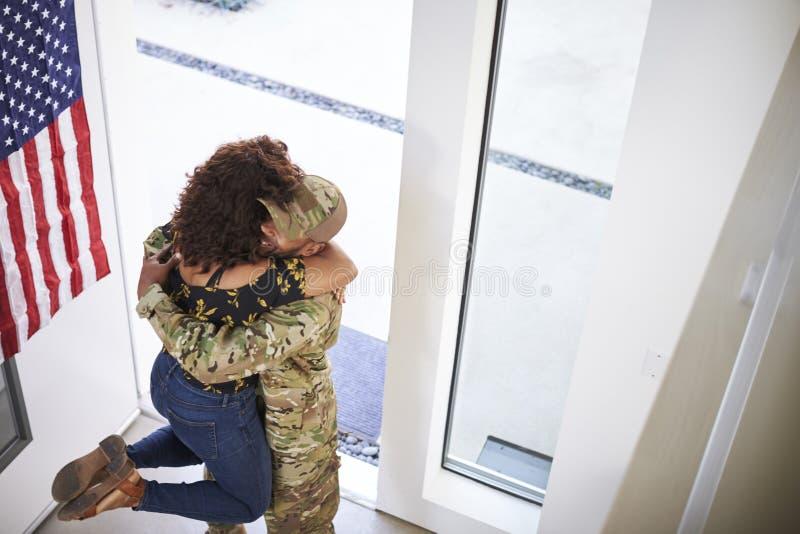 举他的妻子的回来的千福年的非裔美国人的士兵她的在他们的家,高的看法门道入口的脚  免版税库存照片