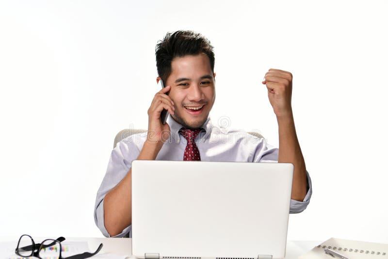 举他的手的商人,当谈话在感到的电话愉快为达到工作时,当使用便携式计算机时 库存图片