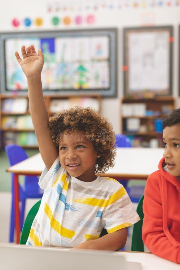举他的手的mixed-race男小学生正面图与他的朋友在他旁边 图库摄影
