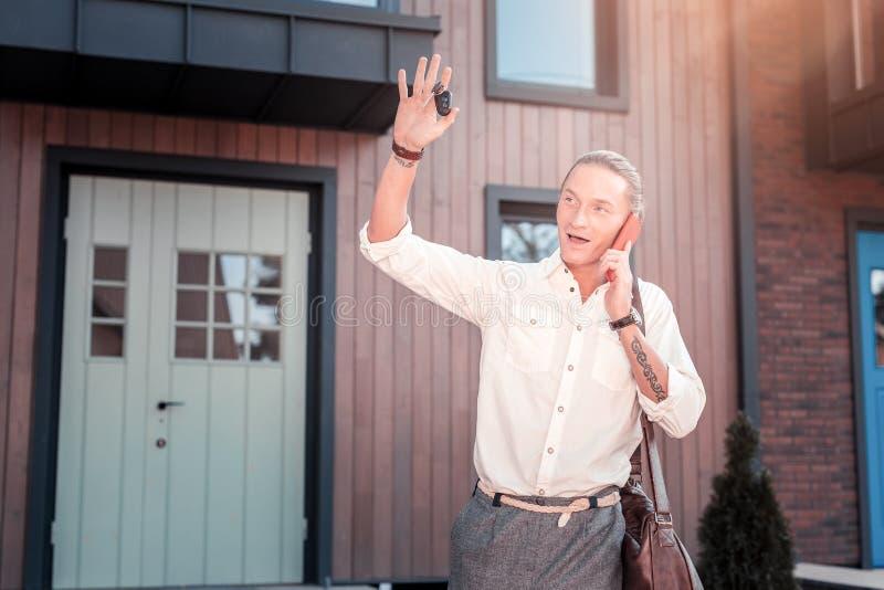 举他的手说法再见的金发的商人到他的家庭 库存照片