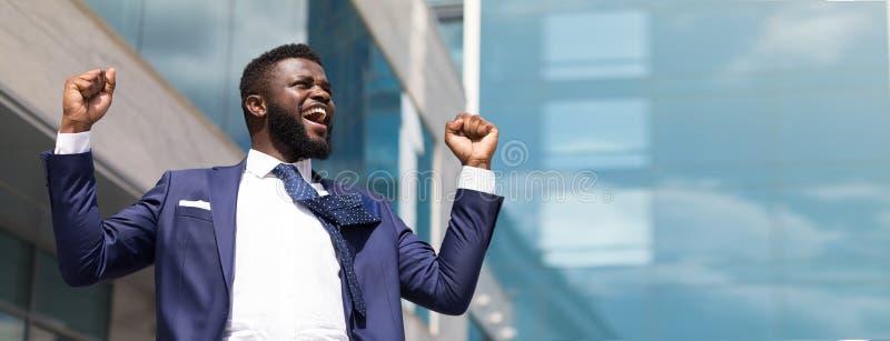 举他的胳膊的年轻愉快的商人 在企业世界上面  免版税库存图片