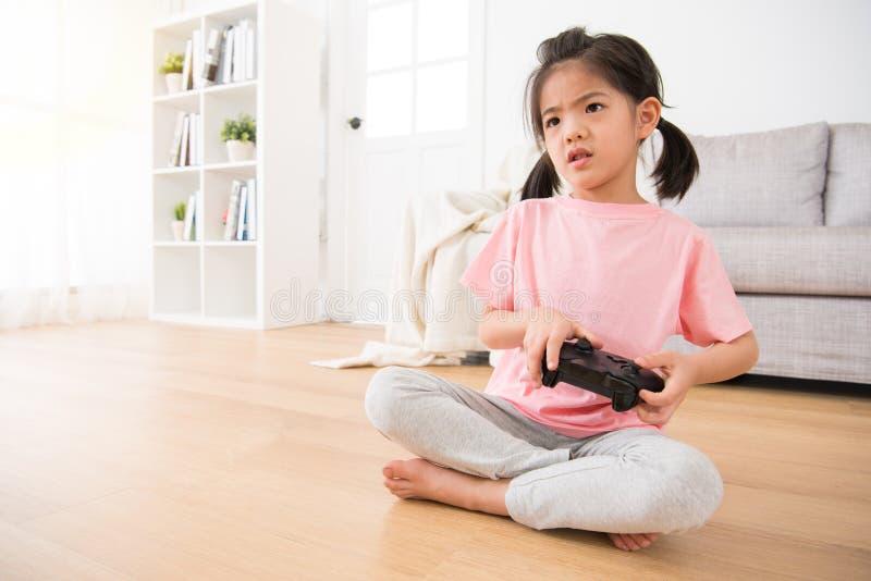 举办比赛控制杆观看的电子游戏的女孩 免版税库存照片