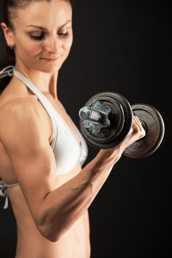 举哑铃的肌肉少妇 免版税库存图片