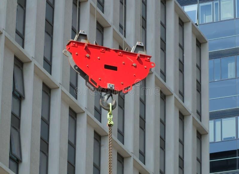 举在一工地工作的一个明亮的红色起重机勾子和滑轮一个暂停的金属链子有都市现代大厦的 免版税库存图片