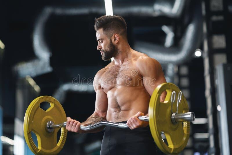 举在健身房的英俊的赤裸举重运动员重的杠铃 免版税图库摄影