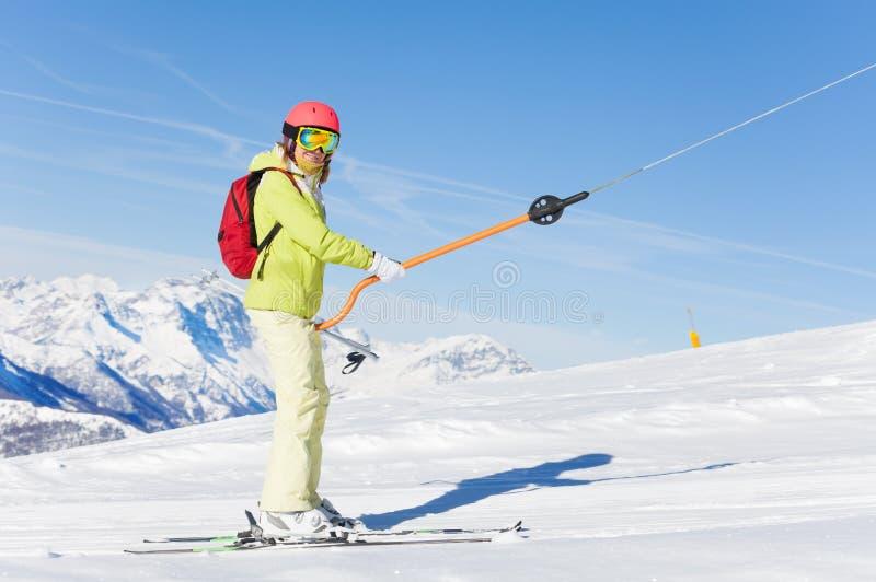 举在按钮推力的女性滑雪者晴天 免版税图库摄影