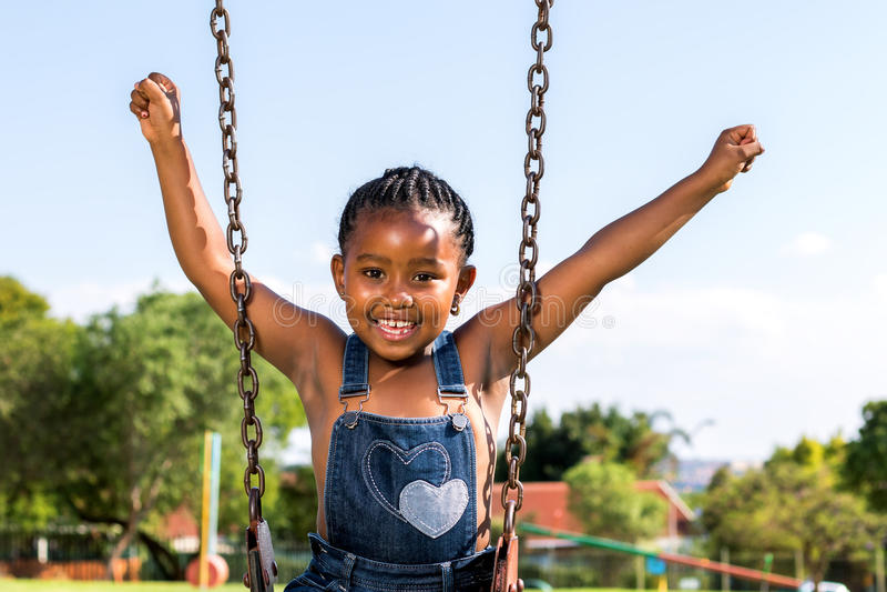 举在摇摆的愉快的非洲孩子胳膊 免版税库存照片