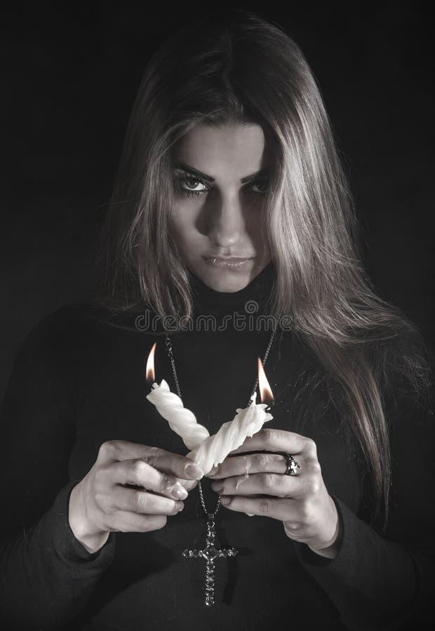 举在烟的妇女两个蜡烛 免版税库存照片