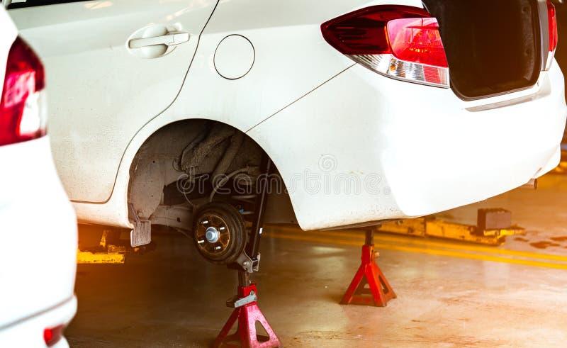 举在车库车间停放的白色汽车和改变轮胎和维护 自动服务业 汽车零件概念 库存照片