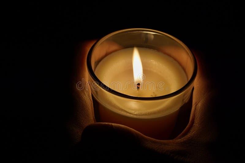 举在透明玻璃发光的男性手一个蜡烛在黑暗中作为沉思、凝思和平静的标志 免版税图库摄影