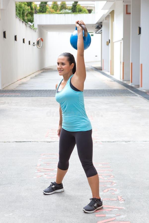 举夺取惯例的蓝色的运动的西班牙妇女蓝色kettlebell户外 图库摄影