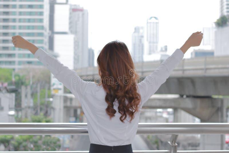 举她的手的后面观点的成功的年轻Aian女商人在都市大厦城市背景 图库摄影