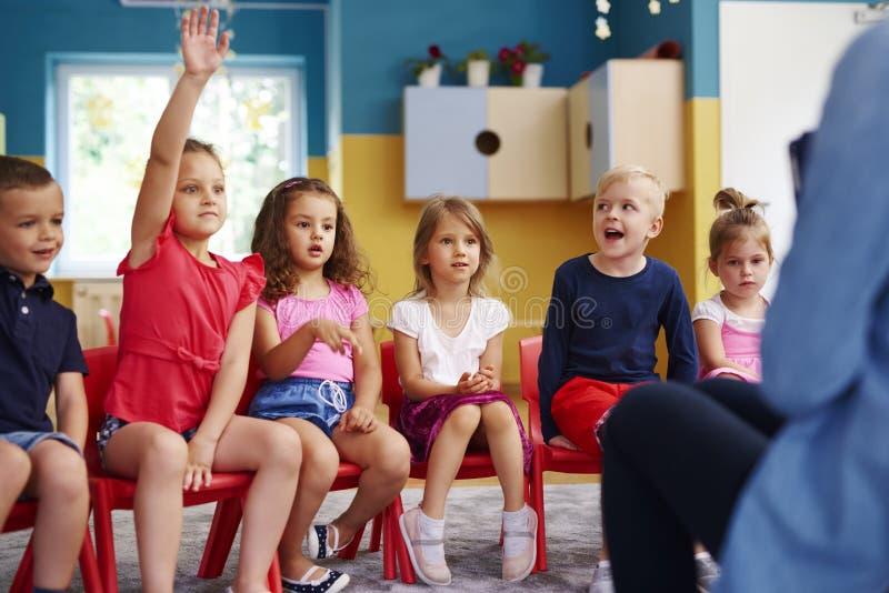 举她的手的女孩问问题在教室 免版税图库摄影
