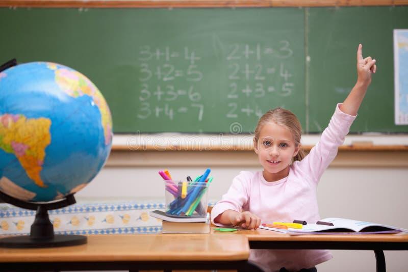举她的手的逗人喜爱的女小学生回答问题 库存照片