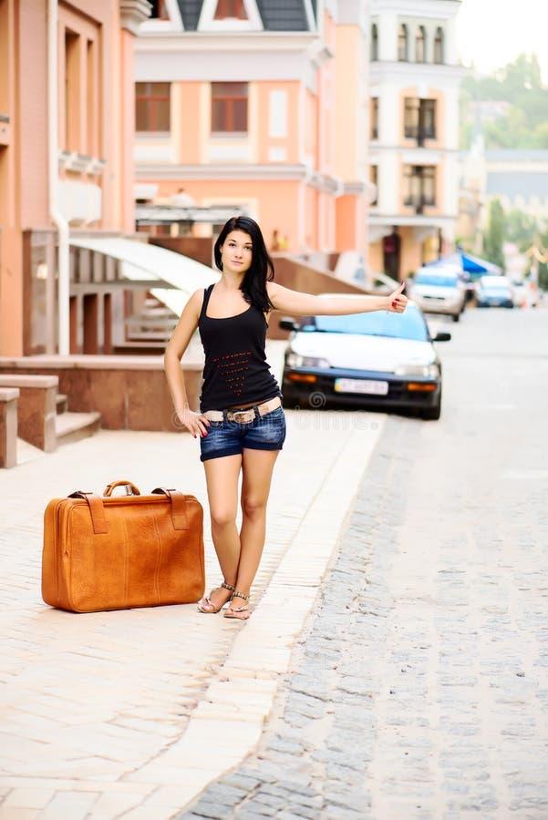 举她的胳膊的少妇叫出租汽车 免版税图库摄影