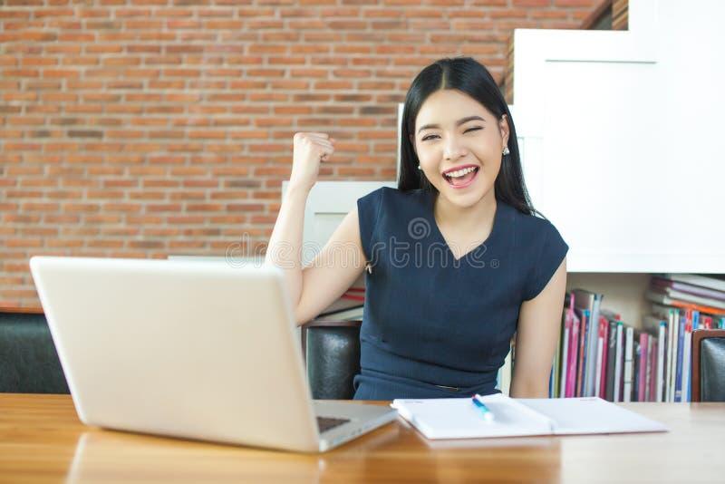 举她的胳膊的激动的亚裔妇女,当研究她的膝上型计算机-成功和企业概念时 免版税库存图片