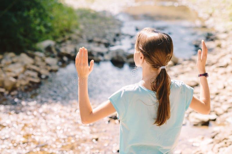 举她的胳膊祈祷在山小河的银行的少女 免版税库存图片