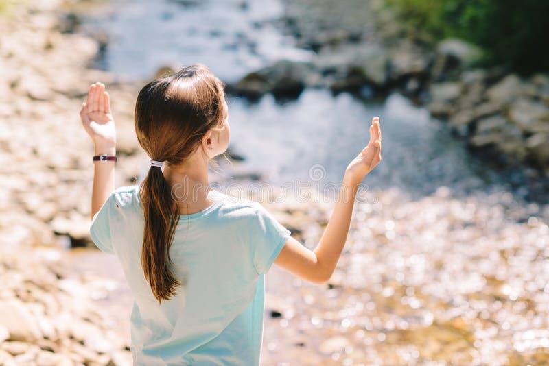 举她的胳膊祈祷在山小河的银行的少女 免版税库存照片