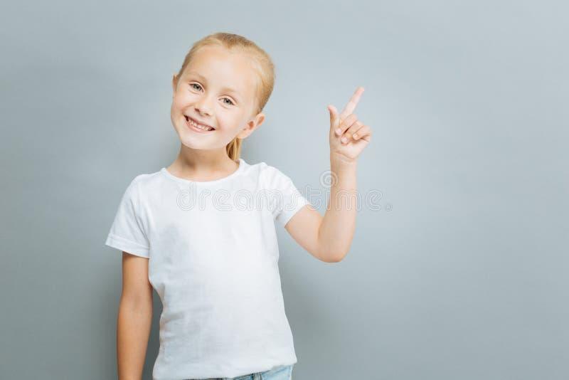 举她的食指的高兴小孩 库存图片
