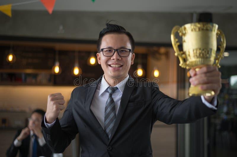 举手和拿着一个金黄战利品杯子的商人对庆祝他成功在使命 优胜者的概念 免版税图库摄影
