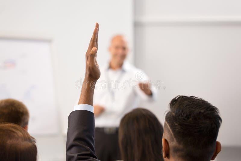 举手的商人在业务会议 免版税库存照片