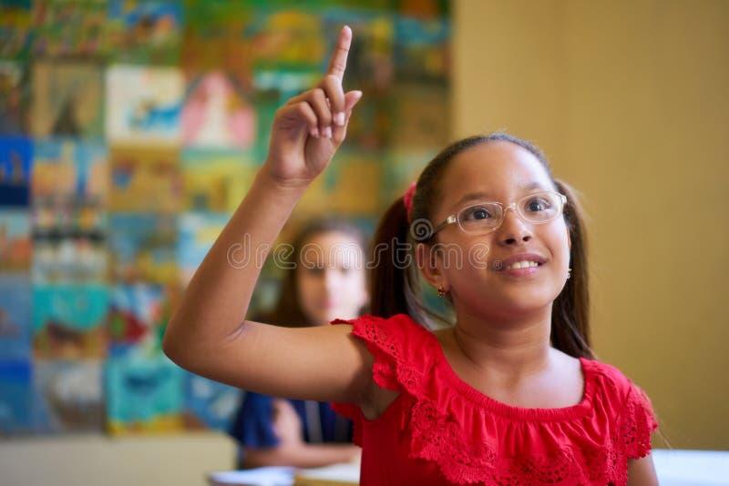 举手的女学生在类的测试期间在学校 库存照片