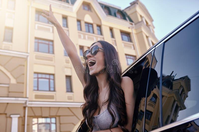 举手的妇女看在车窗外面 免版税库存照片