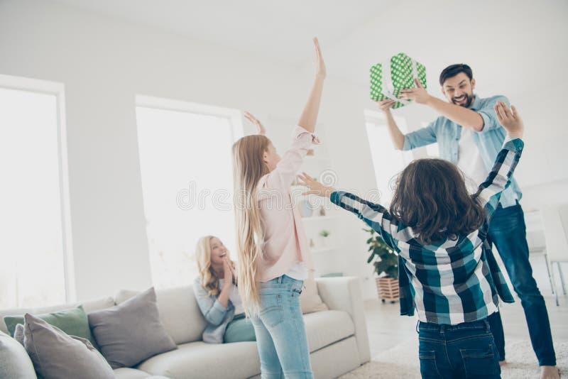 举手的年轻寄养家庭两孩子照片宣扬接受高兴意想不到的giftbox有最佳的父母 免版税库存照片