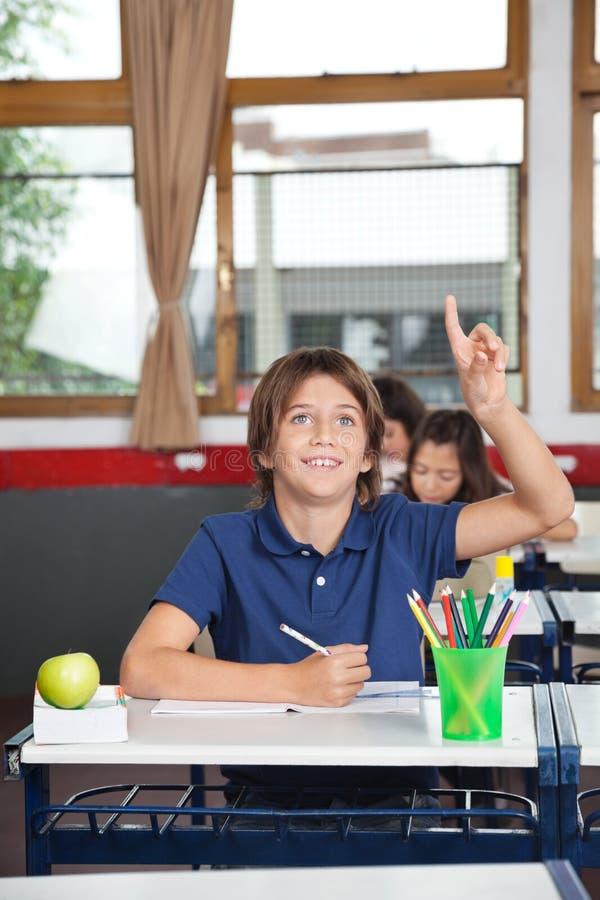 举手的愉快的男小学生在教室 免版税图库摄影