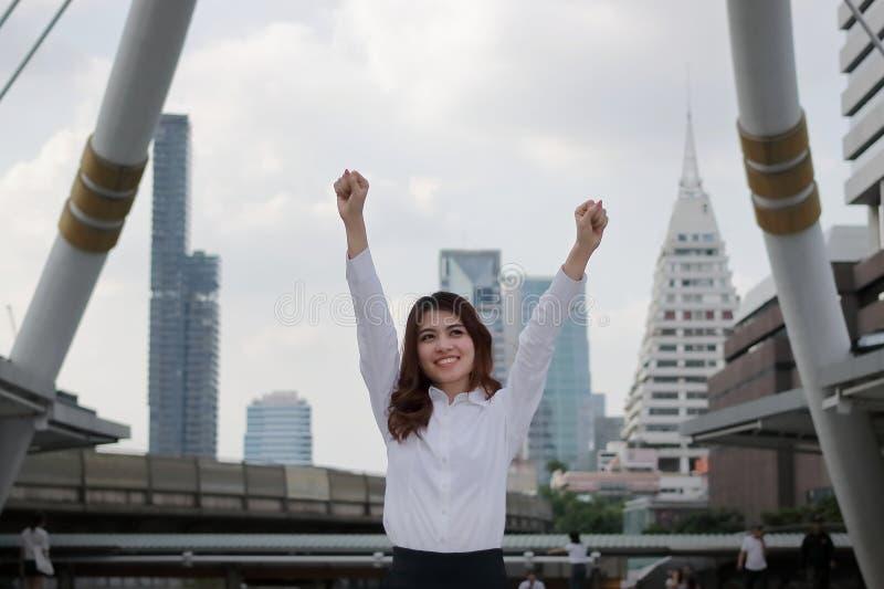 举手的成功的年轻亚裔女商人在都市大厦城市背景 免版税库存图片