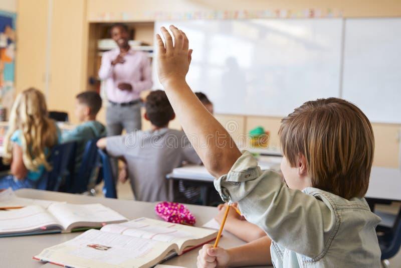 举手的男小学生回答在学校课程的问题 免版税库存照片