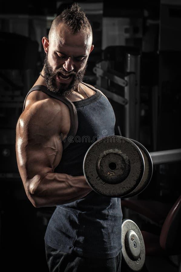 举有些哑铃的肌肉人 免版税库存照片