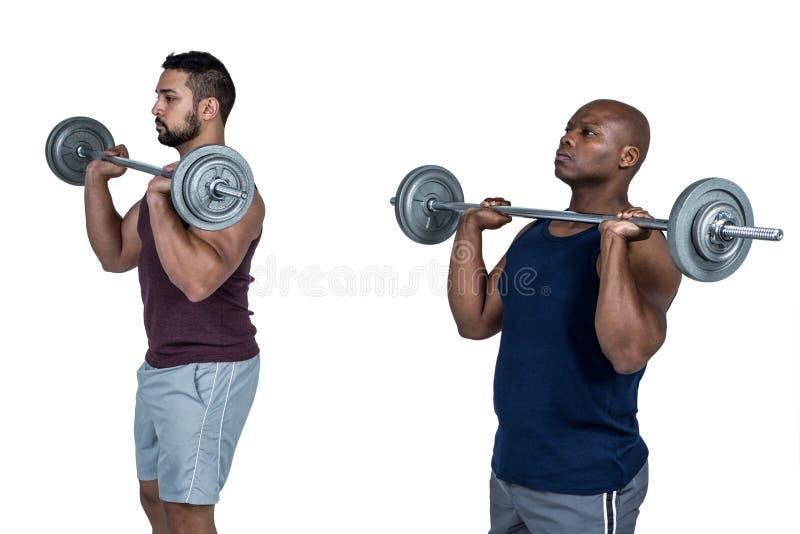 举杠铃的两个肌肉人 免版税库存照片