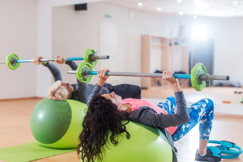 举杠铃的后面观点的两名妇女说谎在稳定球,当行使在健身房时 库存照片