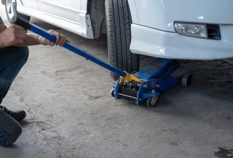 举检查的汽车的水力汽车起重器轮子 免版税库存图片