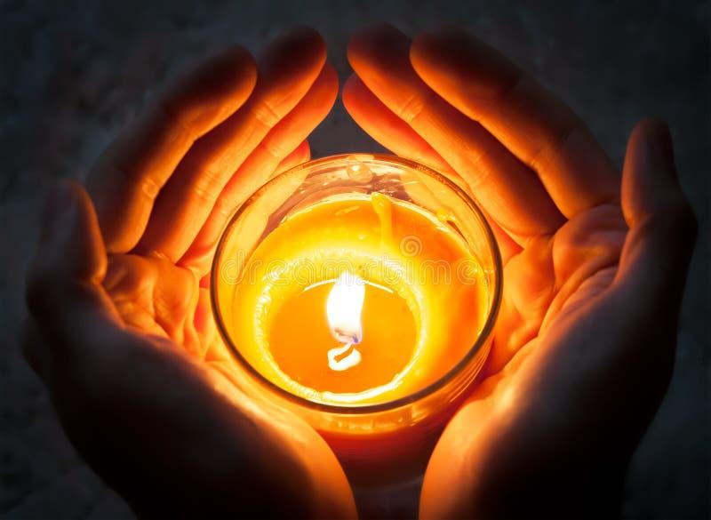 举灼烧的蜡烛的手 免版税库存图片