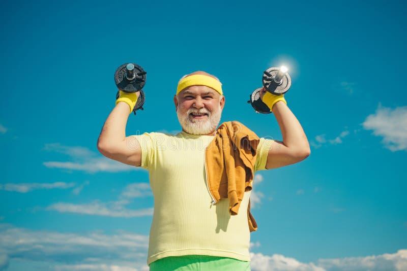 举的老人在他的七十内训练和称 年长年迈的领抚恤金者健康俱乐部或康复中心 库存照片