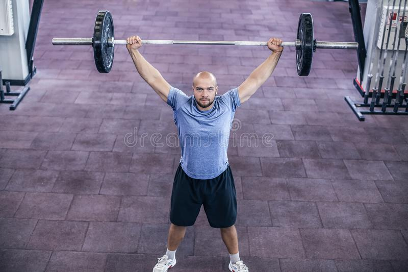 举的重量 运动服举的杠铃的年轻帅哥在健身房 库存照片