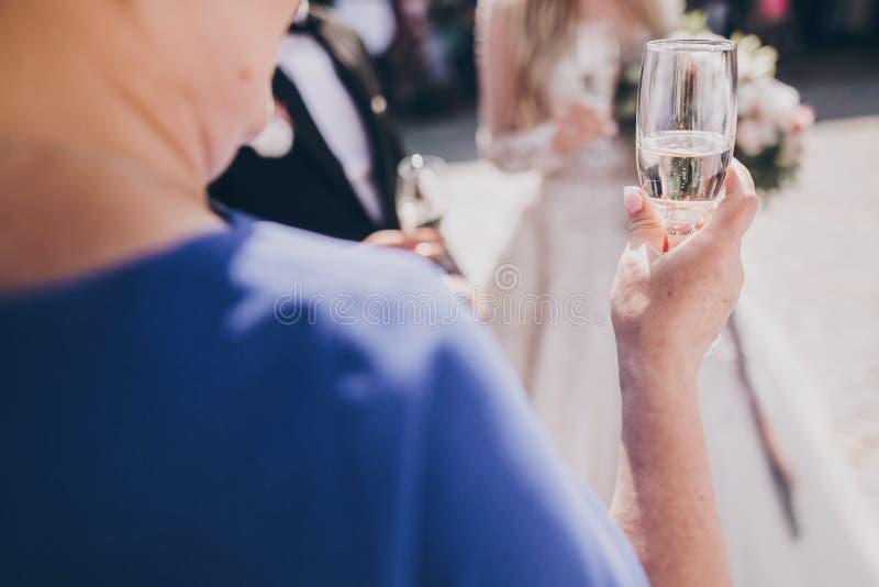 举着香槟酒杯的高级女士,在户外的婚宴上大吃大喝 为新婚祝福的母亲 库存照片