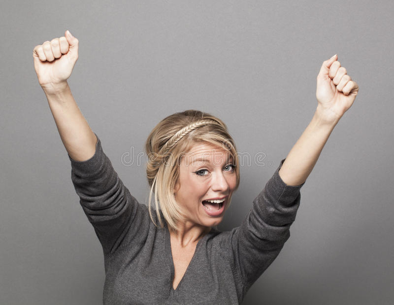举胜利的外向性20s白肤金发的妇女手 免版税库存照片