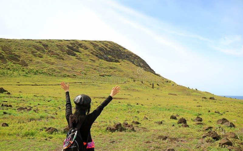 举胳膊的女性游人激动参观Rano Raraku火山,著名Moai雕象的猎物在智利的复活节岛的 图库摄影